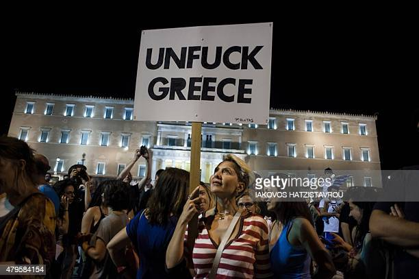 A woman holds a placard as people celebrate in front of the parliament on July 5 2015 in Athens after early results showed those who rejected further...