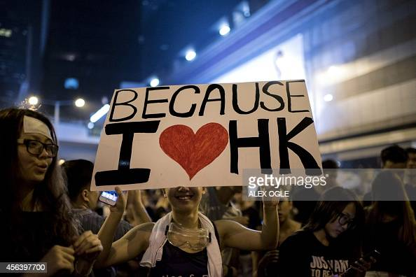 A woman holds a placard at a large prodemocracy protest in Hong Kong on October 1 2014 Hong Kong has been plunged into the worst political crisis...