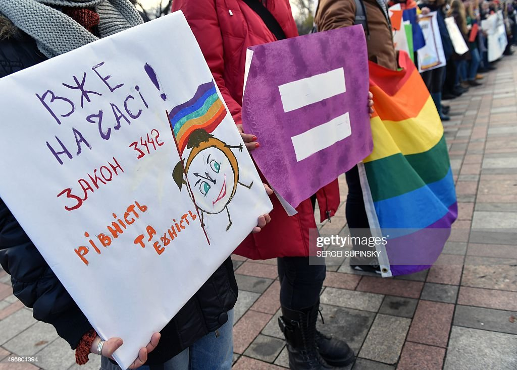 A woman holds a placard bearing an alarm clock with a rainbow flag and reading 'It's time The bill N3442 is equality and dignity' during a...