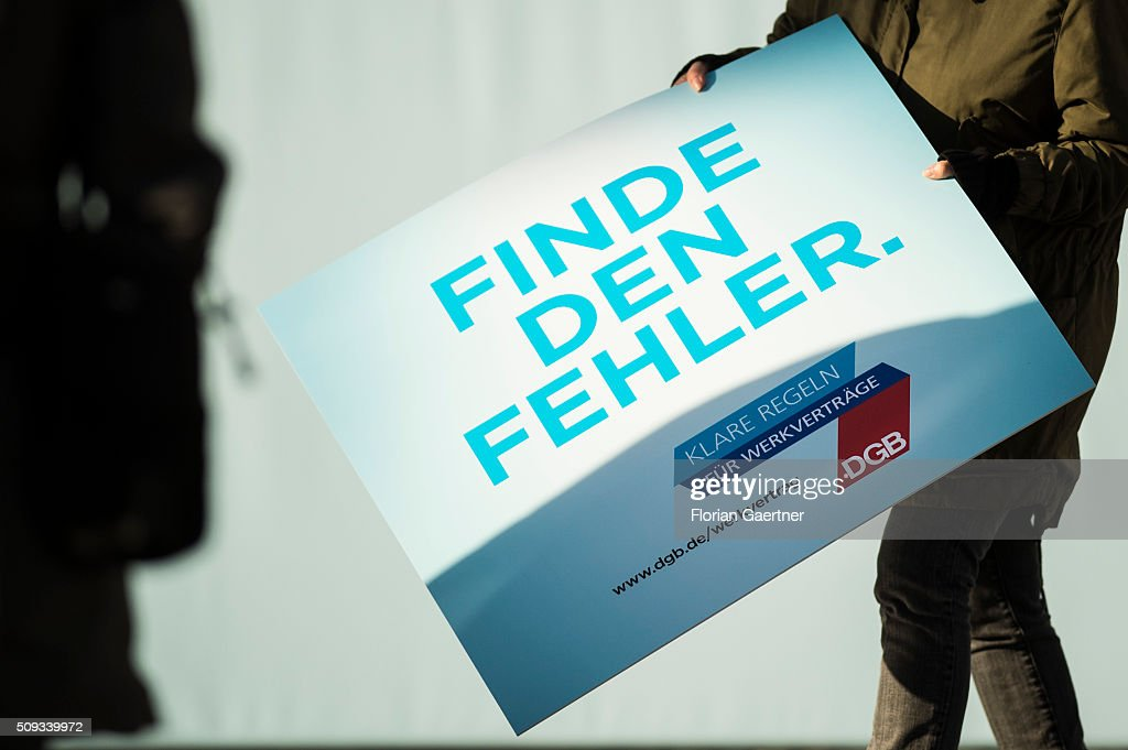 A woman holds a placard before an action of the German Confederation of Trade Unions (DGB - Deutscher Gewerkschaftsbund) on February 10, 2016 in Berlin. The action picks out as a central theme the conditions of service contracts.