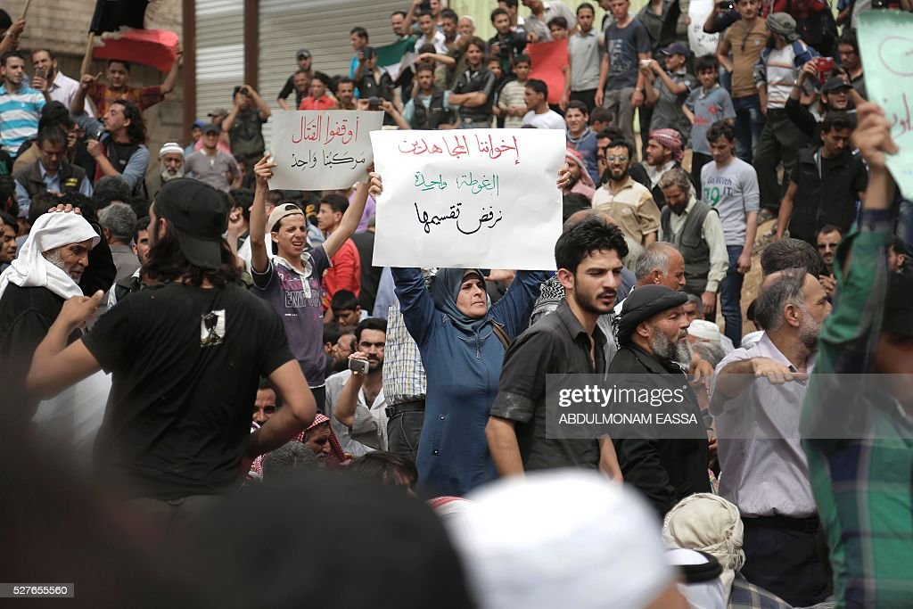 A woman holds a placard during a demonstration calling on all rebel-factions to end the fight and stop the killings in Aleppo, in the town of Mesraba in the eastern Ghouta region, a rebel stronghold east of the Syrian capital Damascus, on May 3, 2016. The writing in Arabic reads (R to L): 'Our mujahideen brothers, Ghouta is one, we refuse to divide it', 'Stop the fighting, we're on the same boat'. Russia said Tuesday it hoped a new ceasefire could be announced within hours for Syria's battered city of Aleppo, where fresh fighting left at least 16 dead including in rocket fire on a maternity hospital. / AFP / ABDULMONAM