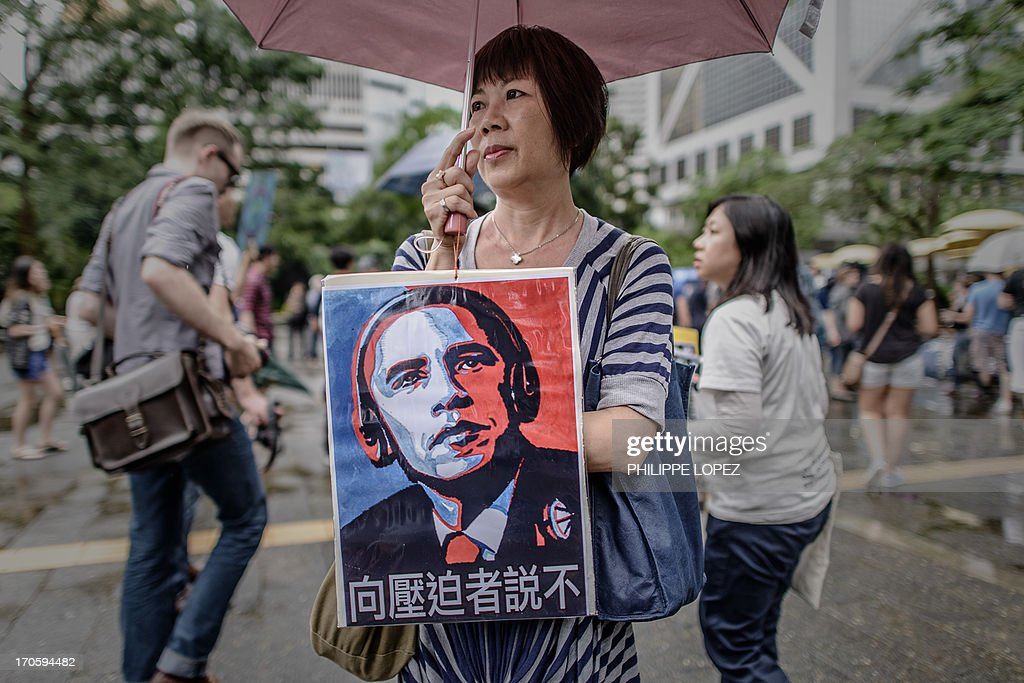A woman holds a placard during a protest march to the US consulate in support of Edward Snowden from the US in Hong Kong on June 15, 2013. Snowden, a former CIA technical assistant, is in hiding in Hong Kong after he arrived in the city on May 20 and blew the lid on a vast electronic surveillance operation by the National Security Agency, which has hit targets in China and Hong Kong. AFP PHOTO / Philippe Lopez