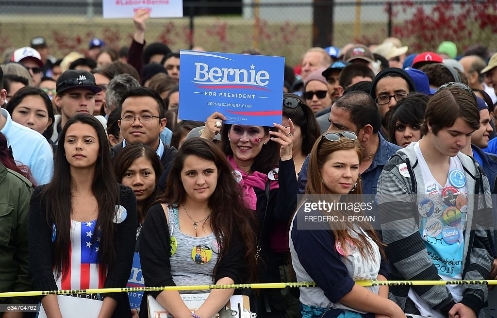 A woman holds a placard in support of Democratic Party candidate Bernie Sanders on May 27, 2016 as a crowd grows ahead of his arrival to speak to supporters in the San Pedro port district of Los Angeles, California. / AFP / FREDERIC
