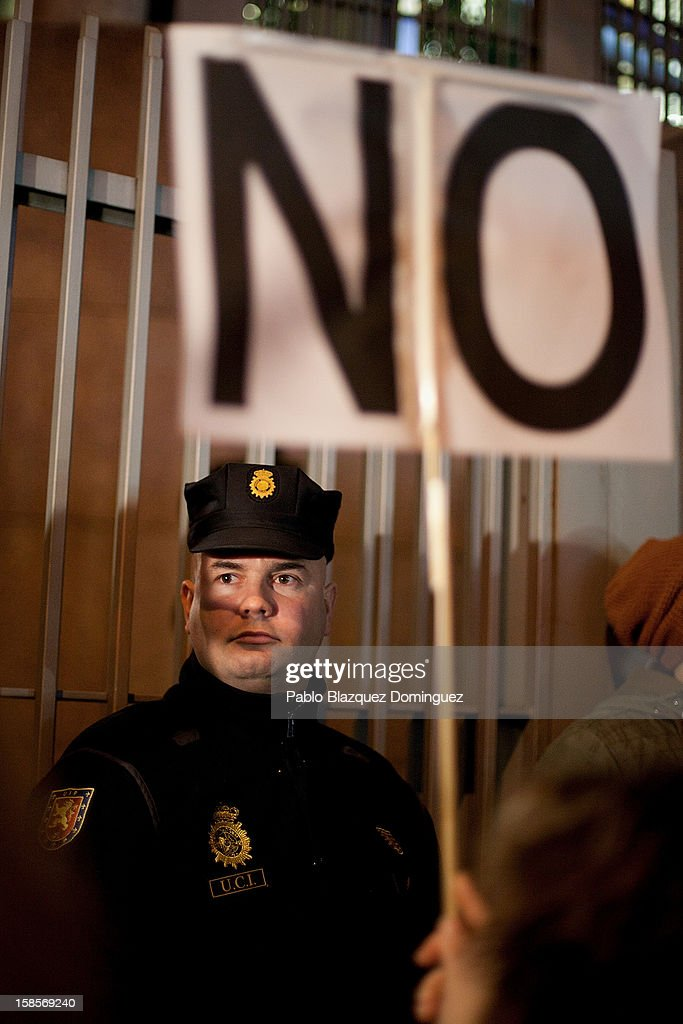 A woman holds a placard next to a riot policeman during a health care workers demonstration outside Madrid Regional Asembly on December 19, 2012 in Madrid, Spain. As of today, health workers unions are calling for a third 48-hour strike against cuts on public health care and the privatization of medical centers and hospitals.
