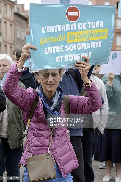 A woman holds a placard of the 'Soulager mais pas tuer' association against euthanasia during a demonstration in front of the prefecture of Toulouse...