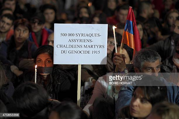 A woman holds a placard reading '500000 Syriacs Assyrians Chaldeans martyrs of 1915 genocide' in Marseille southeastern France on April 23 during a...