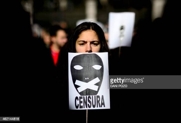 A woman holds a placard reading 'censorship' as she takes part in a demonstration called by the 'Dignity Marches' platform against the new public...