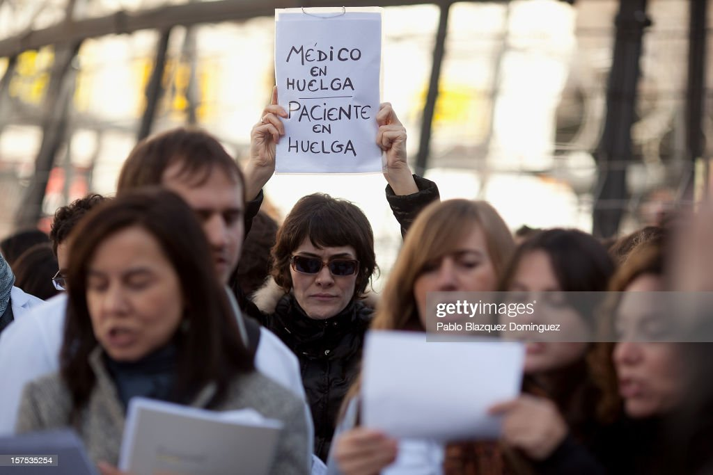 A woman holds a placard reading 'Doctor on strike. Patient on strike' amid other health workers during a demonstration at Puerta del Sol Square on December 4, 2012 in Madrid, Spain. All trade unions called for the second 48 hours health workers' general strike in Madrid region, after Regional Government announced severe cuts and privatization of Medical Centers.