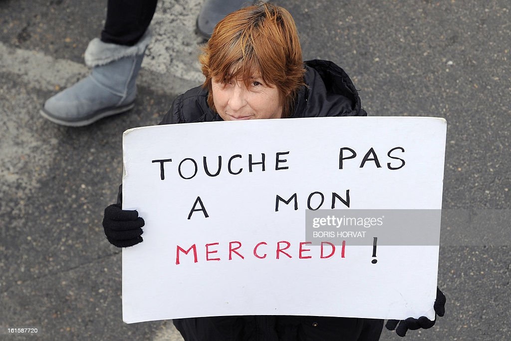A woman holds a placard reading 'Don't touch my wednesday' during a teacher rally, on February 12, 2013 in Marseille, as part of a nationwide strike day over the government's plans to make children attend classes five days a week, instead of the current four. The government recently issued a decree introducing a half day of school on Wednesdays for children 3 to 11 starting in September, while reducing the school day by 45 minutes the rest of the week.