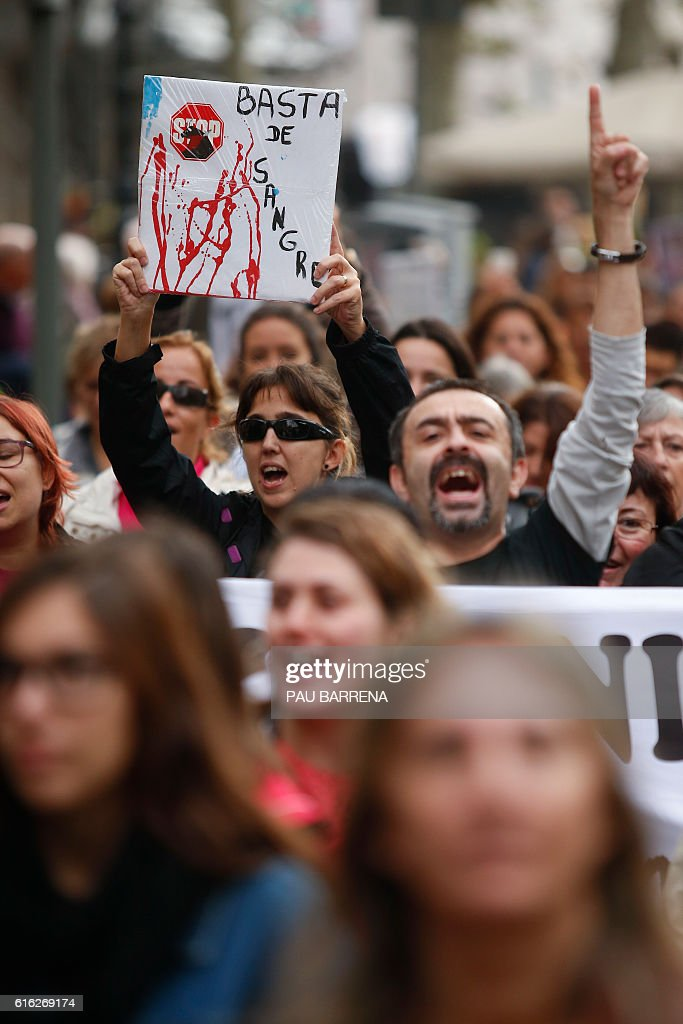 A woman holds a placard reading 'Enough blood' during a pro-animal protest against the recent Spain's Constitutional Court cancellation of a ban on bullfighting in Catalonia, in Barcelona on October 22, 2016. Spain's Constitutional Court on October 20, 2016 cancelled a ban on bullfighting in the region of Catalonia, in what is likely to exacerbate tensions between animal activists and fans of the centuries-old tradition. BARRENA