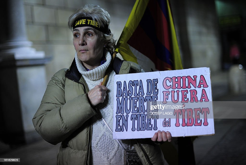 A woman holds a placard reading 'Enough of death in Tibet, China out of Tibet' as she takes part in a demonstration to mark the 100th anniversary of the 1913 Tibetan Proclamation of Independence from China in Barcelona on February 13, 2013.