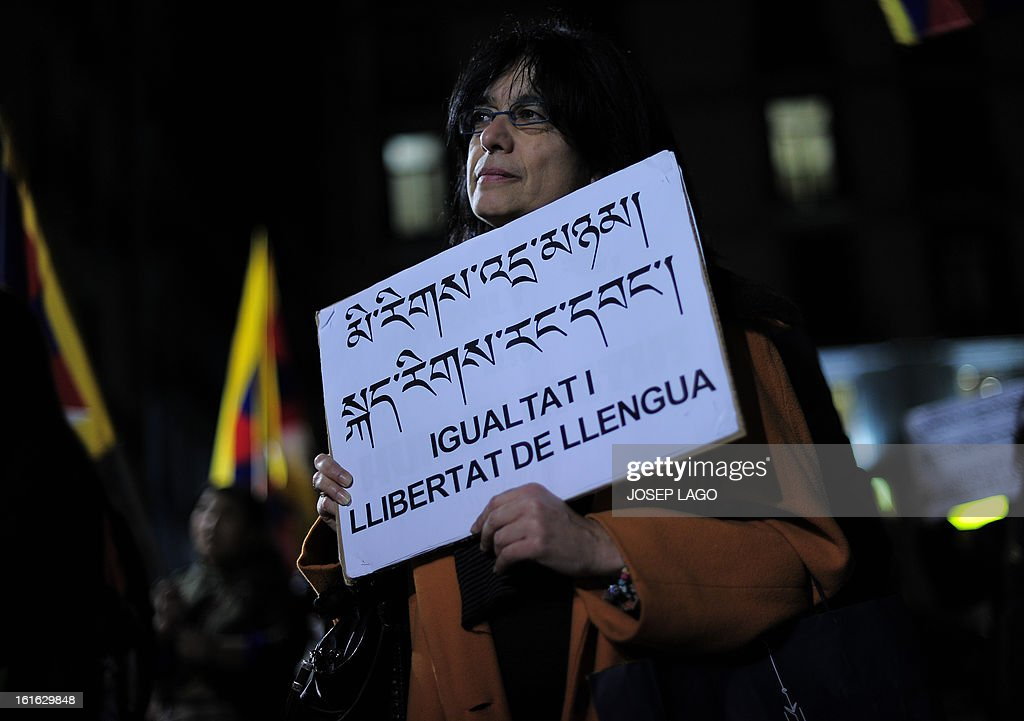 A woman holds a placard reading 'Equality and freedom of language' as she takes part in a demonstration to mark the 100th anniversary of the 1913 Tibetan Proclamation of Independence from China in Barcelona on February 13, 2013. AFP PHOTO / JOSEP LAGO