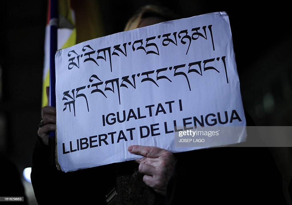 A woman holds a placard reading 'Equality and freedom of language' as she takes part in a demonstration to mark the 100th anniversary of the 1913 Tibetan Proclamation of Independence from China in Barcelona on February 13, 2013.
