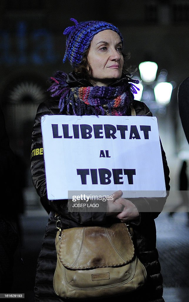 A woman holds a placard reading 'Freedom in Tibet' as she takes part in a demonstration to mark the 100th anniversary of the 1913 Tibetan Proclamation of Independence from China in Barcelona on February 13, 2013.