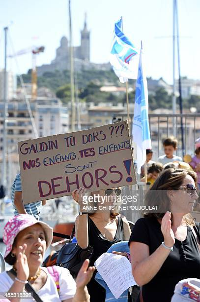 A woman holds a placard reading 'Gaudin are you sleeping OUR children YOUR children are outside' during a demonstration by parents and children in...