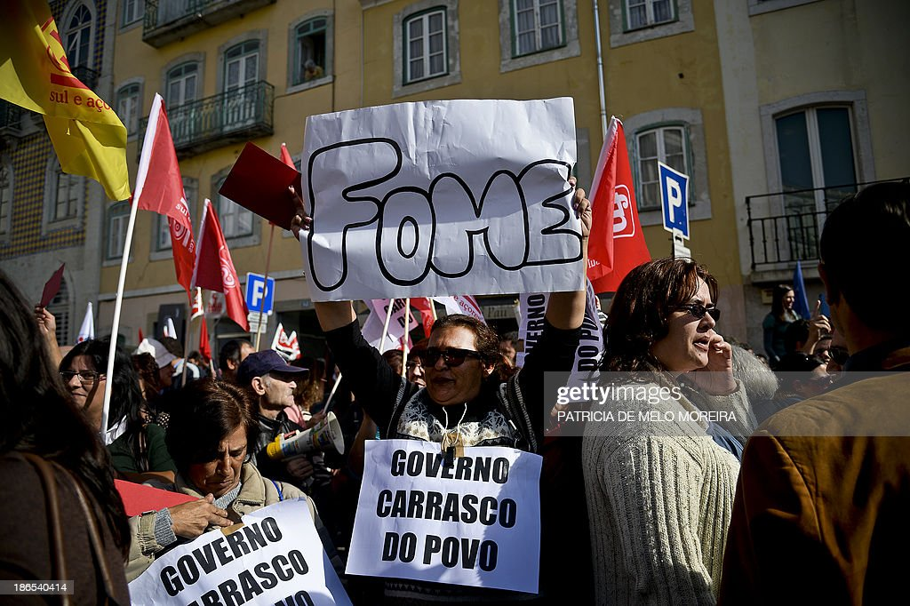 A woman holds a placard reading 'Hunger' during a protest called by the main workers union CGTP against the 2014 State Budget in front of the Parliament in Lisbon on November 1, 2013. Thousands of demonstrators protested in Portugal today against salary cuts and public sector reforms planned in the government's 2014 budget under the country's international bailout deal. After nearly three years of belt-tightening, the budget aims to save a further 3.9 billion euros (5.3 billion USD), partly through cutting public sector salaries and pensions.