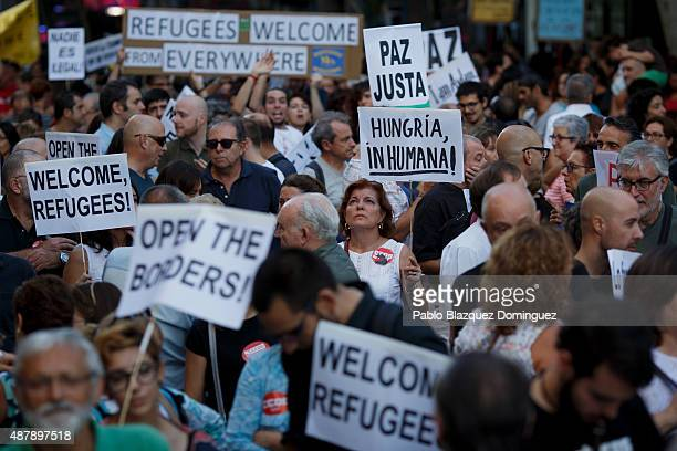 A woman holds a placard reading 'Inhuman Hungary' as others hold placards reading 'Welcome refugees' 'Open the borders' 'Just peace' and 'Refugees...