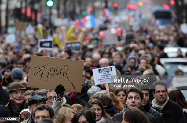 A woman holds a placard reading 'Love' during a Unity rally Marche Republicaine on January 11 2015 at the Place de la Republique in Paris in tribute...