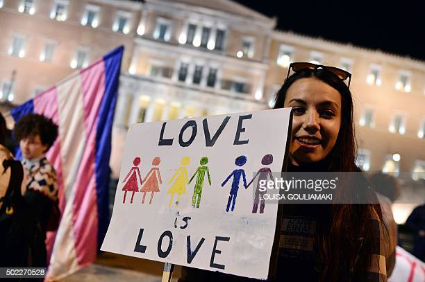 A woman holds a placard reading 'Love is love' during a demonstration of gay rights activists and members of the Athens LGBT community outside the...