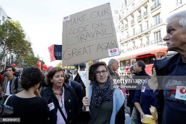 A woman holds a placard reading 'Make our labour laws great again' during a rally to protest the French government's proposed reforms in labour laws...