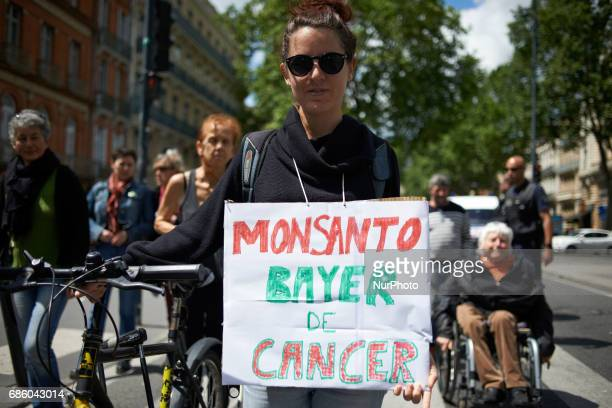 A woman holds a placard reading 'Monsanto Bayer Cancer' People march in Toulouse for the International March against Monsanto as elsewhere in Europe...