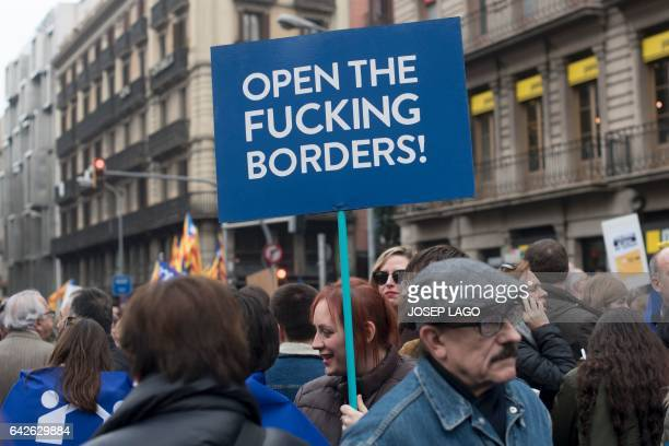 A woman holds a placard reading 'Open the fucking borders' during a demonstration to demand to welcome refugees in Barcelona on February 18 2017 Some...