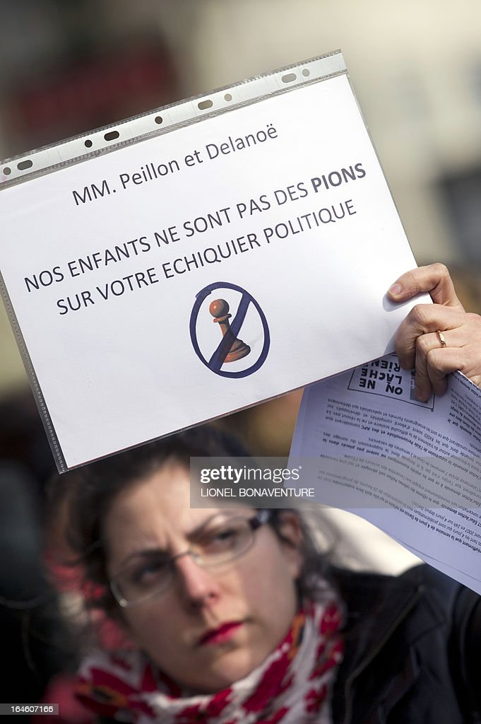 A woman holds a placard reading 'Our children are not pawns on your political chessboard' during a demonstration against the application for the 2013-2014 schoolyear of a reform law increasing the class time of primary school students in front of Paris' city hall, on March 25, 2013, as Paris' municipal council gathers to vote the law's application.