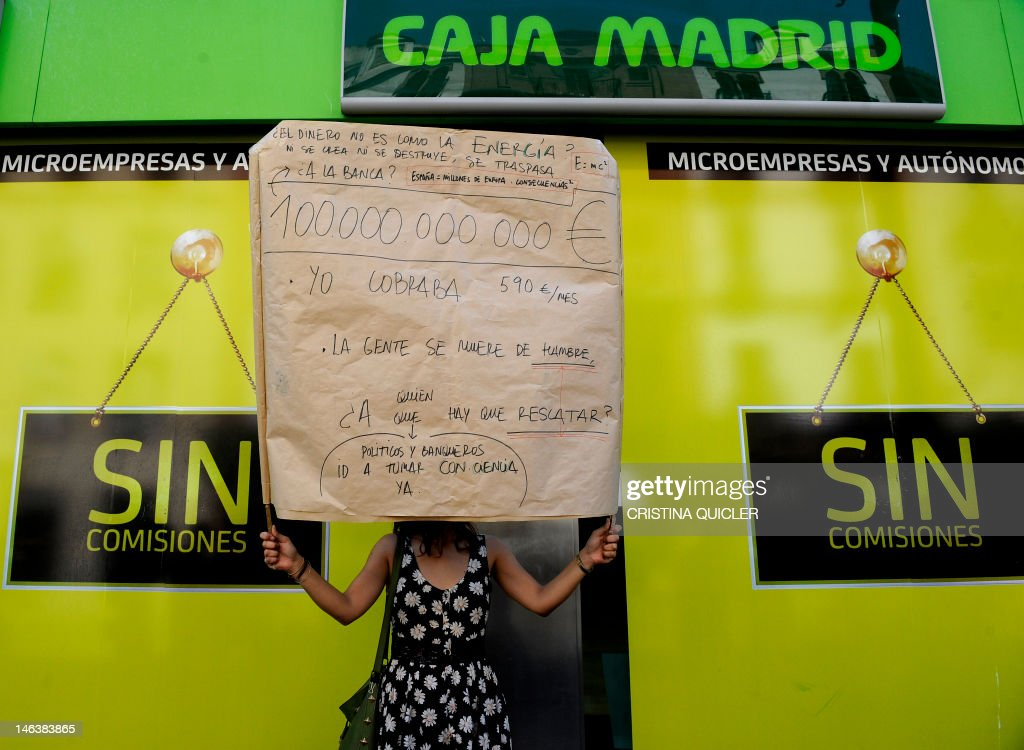 A woman holds a placard reading 'People are starving' during a demonstration in front of a Bankia office in Sevilla, on June 15, 2012. Spain's 'indignant' activists filed a criminal complaint on June 14, 2012 against the former management of Bankia, whose partial nationalisation helped push Madrid to seek a massive EU bailout. The lawsuit targets former Bankia president Rodrigo Rato, who also headed the International Monetary Fund between 2004 and 2007, and other members of the bank's board who oversaw its stock market listing in July 2011.