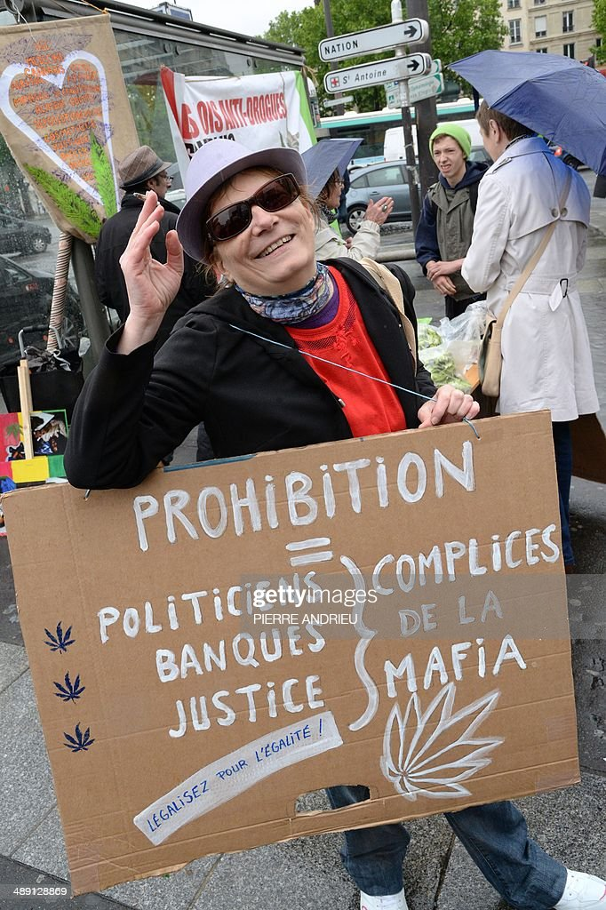 A woman holds a placard reading 'Prohibition equals politicians, banks, justice, all accomplices of the Mafia' as she takes part in a protest to call for the legalization of marijuana on May 10, 2014 in Paris. About 147 million people globally -- or about 2.5 percent of the population -- use cannabis, according to the World Health Organization. AFP PHOTO / PIERRE ANDRIEU