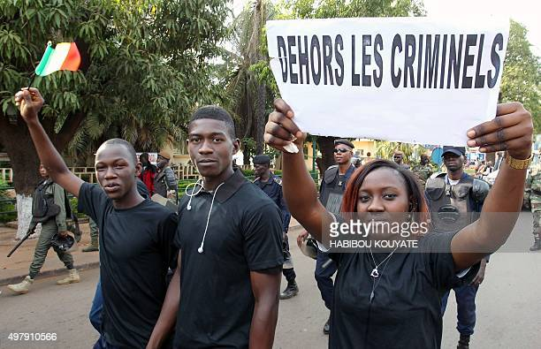 A woman holds a placard reading 'Put outside criminals' during a march on November 19 2015 in Malian capital Bamako to pay tribute to victims of the...