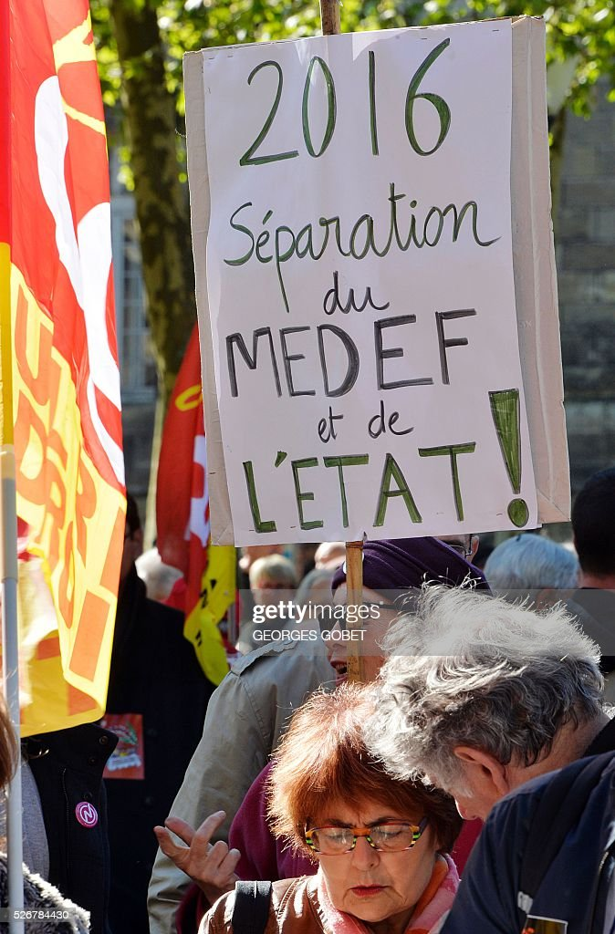 A woman holds a placard reading 'Separation of MEDEF (France's largest employer federation) and State' as she demonstrates in the streets of Bordeaux during the traditional May Day rally on May 1, 2016. / AFP / GEORGES