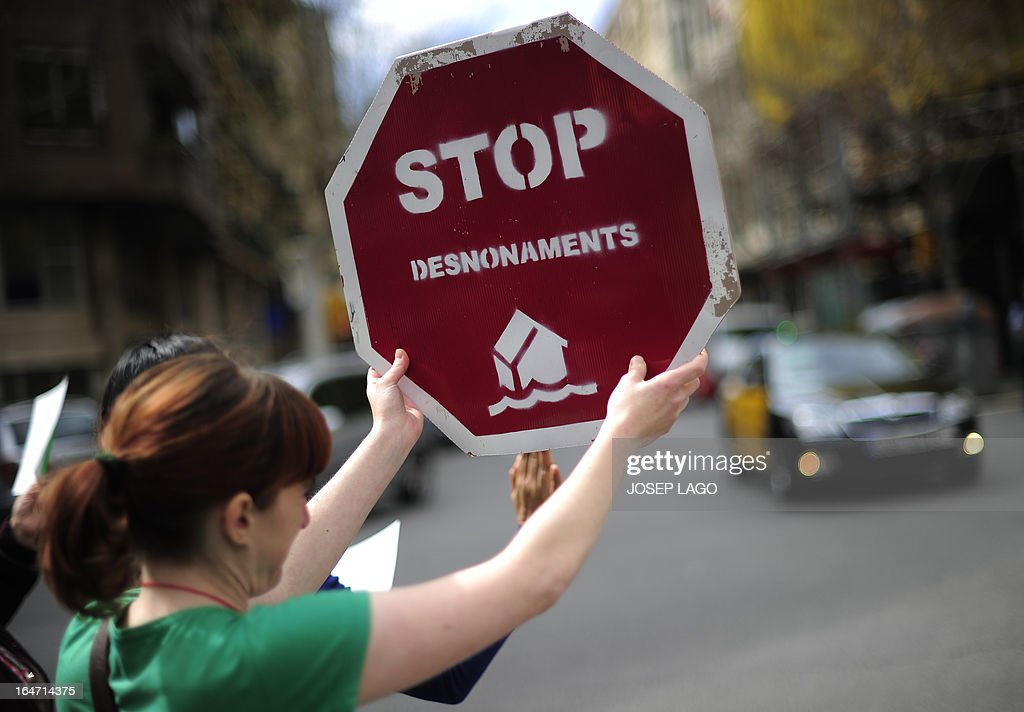 A woman holds a placard reading 'Stop evictions' during a protest by Platform for Mortgage Victims (PAH) to push for a new law to end a wave of evictions of homeowners ruined by the economic crisis, in Barcelona, on March 27, 2013. AFP PHOTO/ JOSEP LAGO
