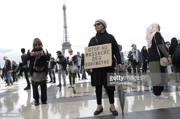 A woman holds a placard reading 'stop to the massacre of Rohingya' as she takes part in a rally in front of The Eiffel Tower in Paris on September 16...