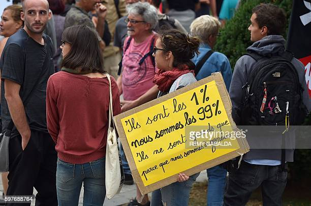 A woman holds a placard reading 'They are the 1% we are the 99% they are big because we are on our knees' as she looks on during a protest against...