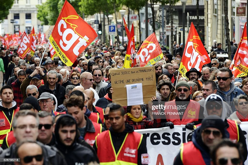 A woman holds a placard reading 'What justice for workers ? Victims for a second time!' as people holding French CGT Trade Union's flags demonstrate in the streets of Marseille during the traditional May Day rally on May 1, 2016. / AFP / Franck PENNANT