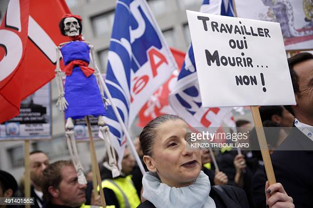 A woman holds a placard reading 'work yes die no' during a demonstration in front of the Air France headquarters in RoissyenFrance on October 5...