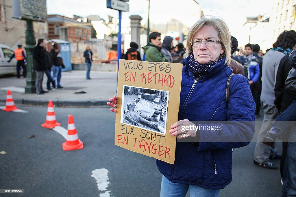 A woman holds a placard reading 'You are late - they are in danger' in the direction of traffic blocked by a demonstration of Afghan refugees on the Wetstraat - rue de la Loi in Brussels on October 29, 2013. AFP PHOTO / BELGA / OLIVIER VIN **BELGIUM OUT**