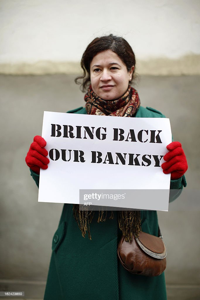 A woman holds a placard that reads 'Bring Back Our Banksy' during a protest next to a section of a wall where celebrated street artist Banksy's 'Slave Labour' graffiti artwork was removed in north London on February 23, 2013. The work that showed a young boy using a sewing machine to make the British flag has been carefully removed and will be auctioned in Miami where it's expected to fetch around 328,000 GBP (500,000 USD). Residents of the North London area have reacted angrily to the removal of the work, but the auction house says the piece was acquired legally. AFP PHOTO / JUSTIN TALLIS