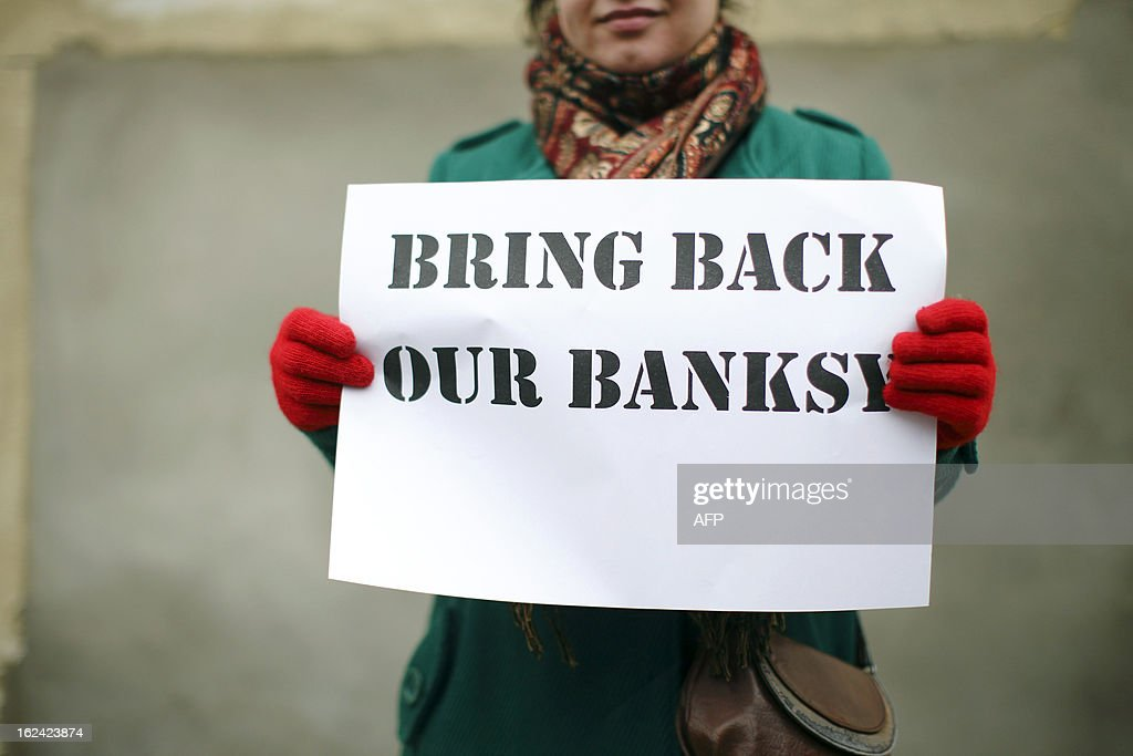 A woman holds a placard that reads 'Bring Back Our Banksy' during a protest next to a section of a wall where celebrated street artist Banksy's 'Slave Labour' graffiti artwork was removed in north London on February 23, 2013. The work that showed a young boy using a sewing machine to make the British flag has been carefully removed and will be auctioned in Miami where it's expected to fetch around 328,000 GBP (500,000 USD). Residents of the North London area have reacted angrily to the removal of the work, but the auction house says the piece was acquired legally.