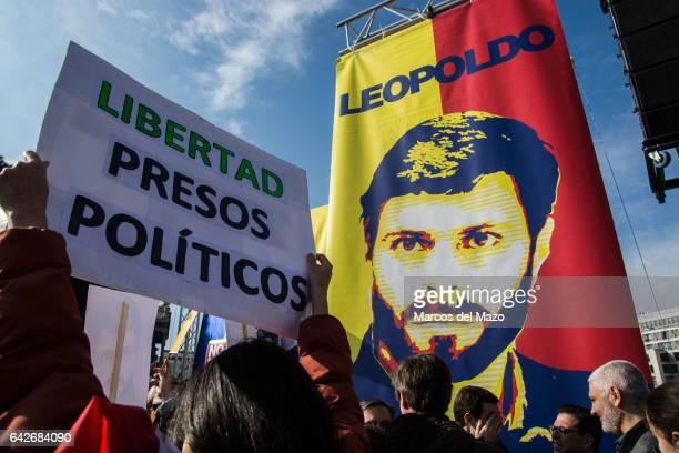 A woman holds a placard that reads 'freedom political prisoners' during a protest demanding the release of Leopoldo Lopez and political prisoners