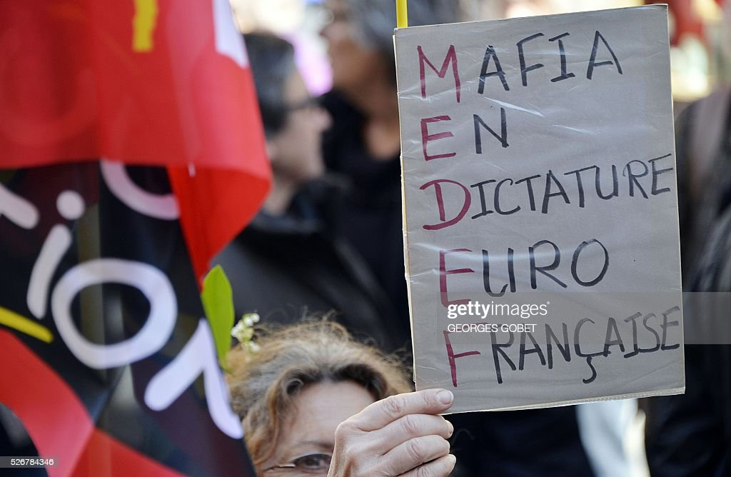 A woman holds a placard using each letter of MEDEF, France's largest employer federation, to mean 'French Euro dictatorship mafia' as she demonstrates in the streets of Bordeaux during the traditional May Day rally on May 1, 2016. / AFP / GEORGES
