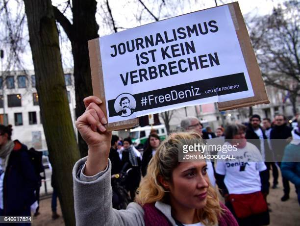 A woman holds a placard with hashtag #FREEDENIZ reading' Journalism is not a crime' to protest the detantion of German journalist Deniz Yucel in...
