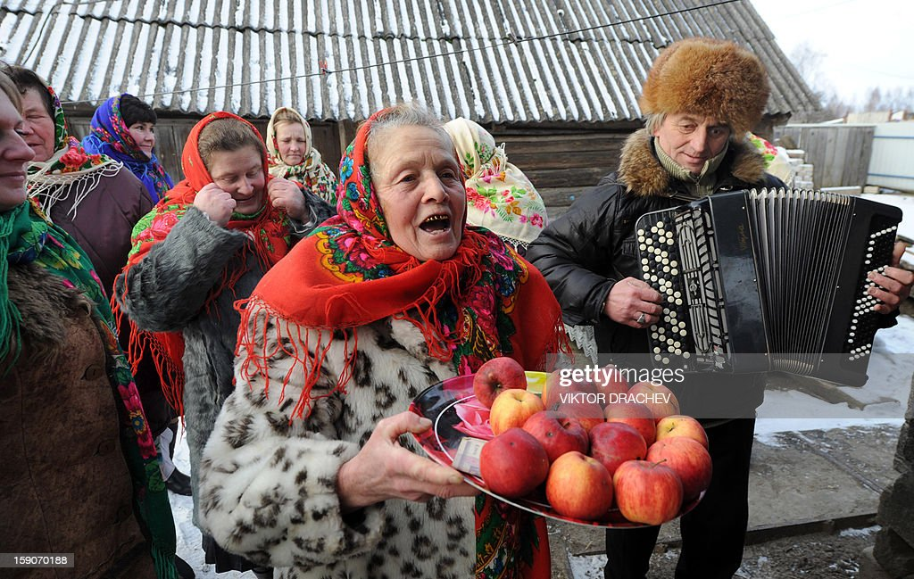A woman holds a plate of apples during Christmas celebration in the town of Richev, some 290 km south from Minsk. on January 7, 2013. Orthodox Christians celebrate Christmas on January 7 in the Middle East, Russia and other Orthodox churches that use the old Julian calendar instead of the 17th-century Gregorian calendar adopted by Catholics, Protestants, Greek Orthodox and commonly used attendsin secular life around the world.