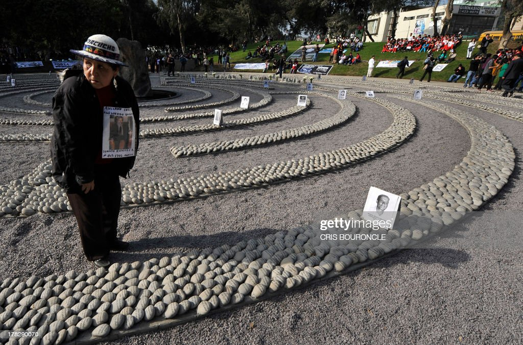 A woman holds a portrait at a symbolic graveyard of stones reading names of victims of the war against terrorist groups as The Shinning Path and the Tupac Amarus during the 80's and 90's, in Lima on August 28, 2013. Relatives of victims commemorate the 10th anniversary of the release of the report of the Commission of Truth and Reconciliation of Peru, which concluded that there were 69.000 people killed or missing during the 80's and 90's.