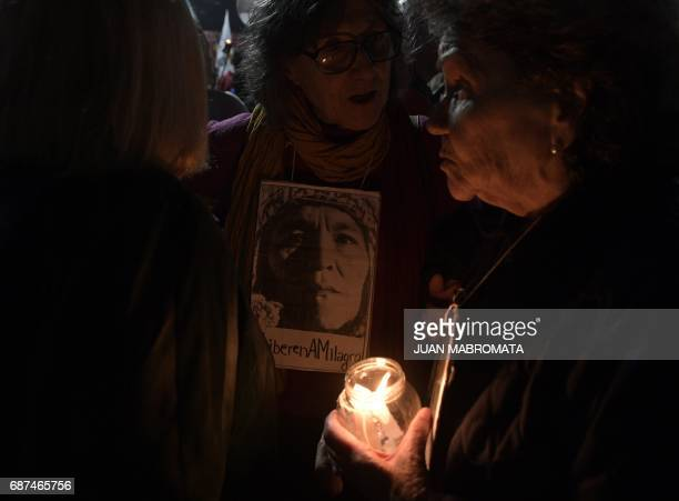 A woman holds a portrait during a march with torches demanding the release of the leader of the Tupac Amaru neighbourhood association activist...