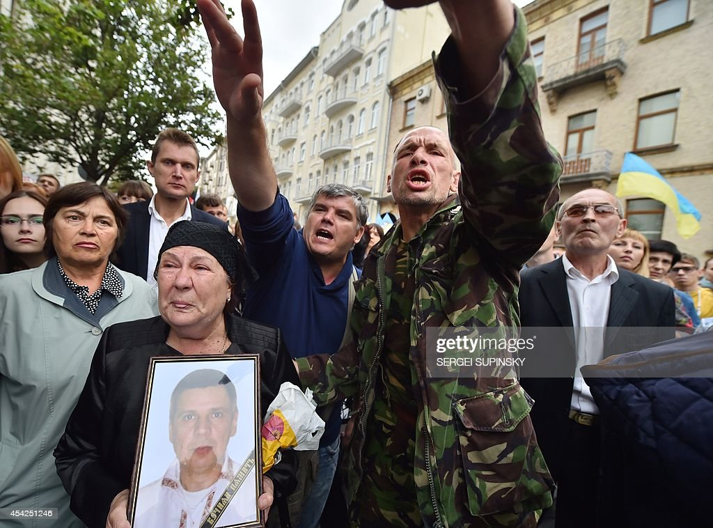 A woman holds a portrait of her dead son, serviceman ofa volunteer battalion, as she speaks during rally in front of Ukrainian President Petro Poroshenko's office in Kiev on August 27, 2014. Protesters demand help for the volunteer battalions of Donbass, Mirotvorets, Kherson and Dnipro-1 surrounded by pro-Russian militants for the fifth day in the small city of Izvaryne, suburb of the eastern Ukrainian city of Donetsk.