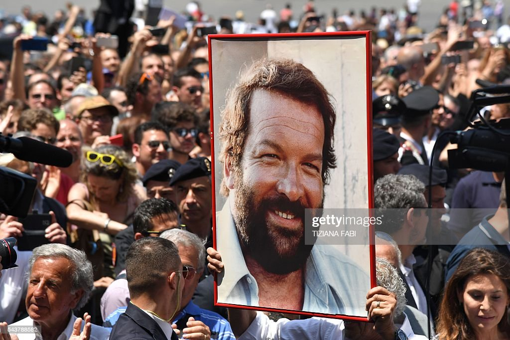 A woman holds a portrait of Italian actor Bud Spencer, born Carlo Pedersoli, outside the church of the artists, Santa Maria in Montesanto, on June 30, 2016 at the end of the funeral of the actor at Piazza del Popolo in Rome. Bud Spencer who starred in a string of spaghetti westerns, died on June 27 in Rome aged 86. Spencer, born in Italy in 1929, played in 16 films alongside Terence Hill, whose real name was Mario Girotti. He was also an Italian swimming champion and in 1950, he became the first Italian to swim the 100-metre freestyle in under a minute. / AFP / TIZIANA