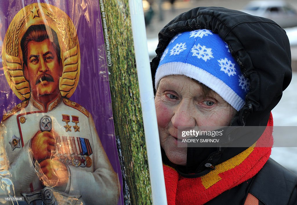 A woman holds a portrait of Soviet dictator Josef Stalin as Russian Communists and their supporters lay flowers at his tomb at the Red Square in Moscow on March 5, 2013, to mark the 60th anniversary of Stalin's death. Russia marks today 60 years since the death of Stalin with attitudes split about whether to view him as a tyrant who slaughtered millions or a national saviour who helped turn the country into a global superpower that emerged victorious in World War II.