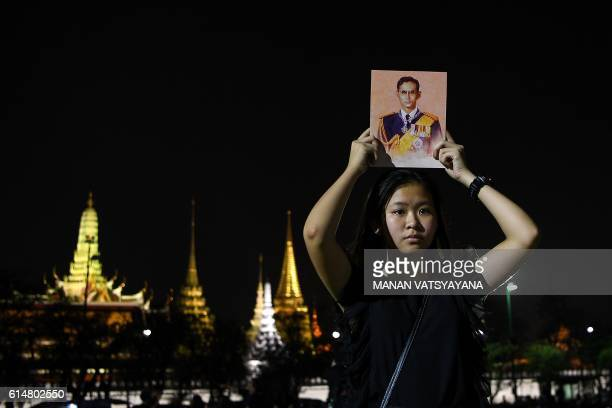 A woman holds a portrait of the late Thai King Bhumibol Adulyadej outside the Grand Palace in Bangkok on October 15 2016 / AFP / MANAN VATSYAYANA