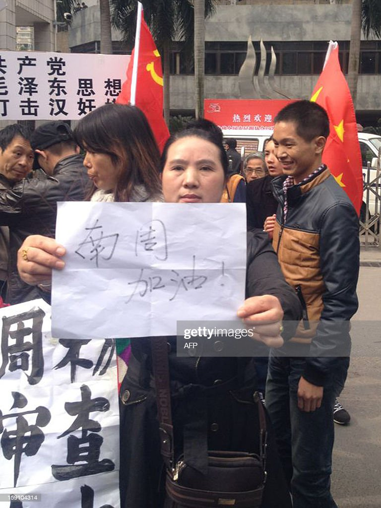 A woman holds a poster reading 'come on, Southern Weekend' to support journalists from the newspaper near their offices in Guangzhou, south China's Guangdong province on January 8, 2013. Chinese bloggers and celebrities along with foreign media campaigners threw their support behind journalists at a newspaper enmeshed in a censorship row on January 8, after a rare protest for press freedom.CHINA